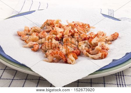 cleaned and cooked crayfish tails with white kitchen paper on a blue plate