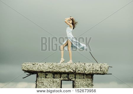 Pretty cute sensitive blonde woman or girl stands with raised hand in blue dress waving on wind outdoor on broken concrete bunker