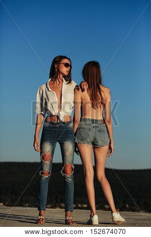 pretty sexy cute girls or women in jeans and shorts topless in sunglasses outdoor on sunny day standing on blue sky background