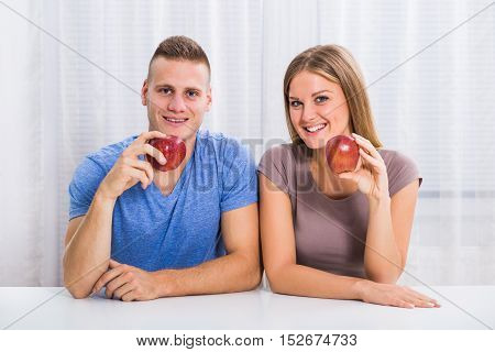 Portrait of young happy couple holding apple.