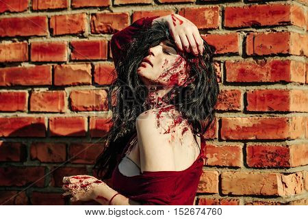 Halloween zombie girl pretty young woman with bloody brunette hair with wounds and red blood outdoors on brick wall