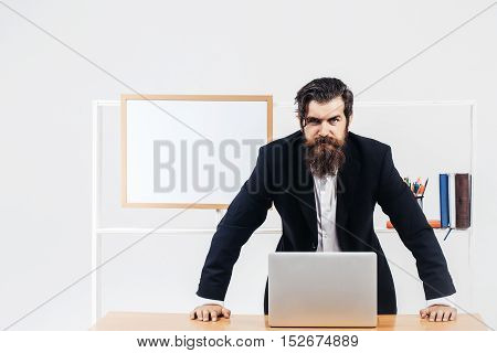 Angry bearded boss in black classic suit standing learning over desk with laptop in office