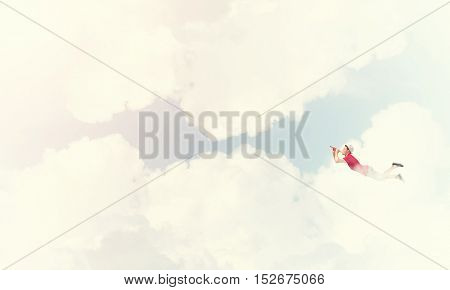 Young cheerful man flying high in sky and playing fife