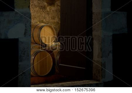 Barrels in a winery, through the door of cellar, Bordeaux Vineyard