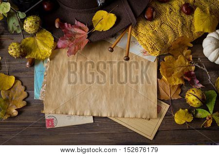 Vintage autumn frame with yellow leaves, chestnuts, hat, camera, knitting needles and retro envelopes on rustic wooden background. Top view point.