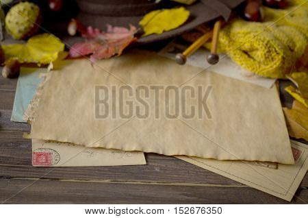 Vintage autumn frame with yellow, red leaves, chestnuts, hat, camera, knitting needles and retro envelopes on rustic wooden background.