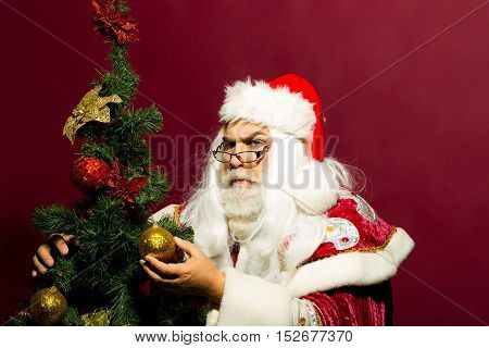 Serious Santa Decorates Christmas Tree