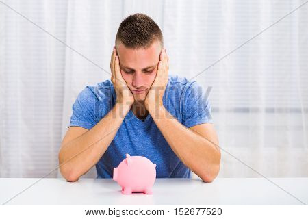Young man is sad because he is having problem with saving money.