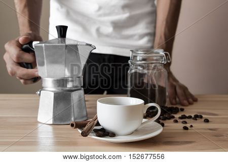 White cup and italian coffee pot. Male hands holding coffee pot ready to pour espresso in the white cup.