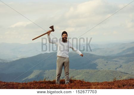 Brutal man bearded hipster with beard and moustache in hat stands with axe on mountain top on cloudy sky