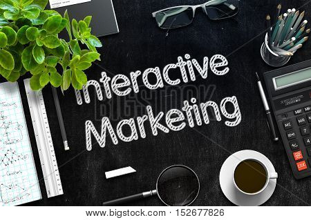 Black Chalkboard with Handwritten Business Concept - Interactive Marketing - on Black Office Desk and Other Office Supplies Around. Top View. 3d Rendering. Toned Image.
