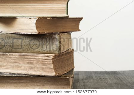 Stack of old books. Stack of old books on dark wood table, in front of white background.