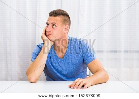 Depressed young man is sitting at the table and thinking about something.