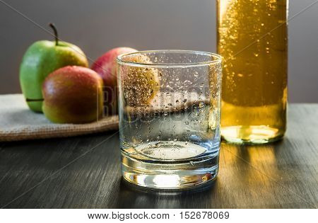 Empty glass, apples, apple wine ready to drink. An empty glass prepared to be poured with cold apple wine, apples in the background.