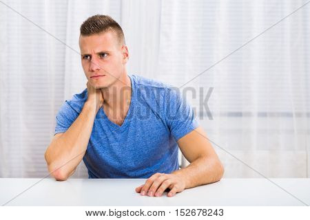 Young man is sitting at the table and having neck pain.