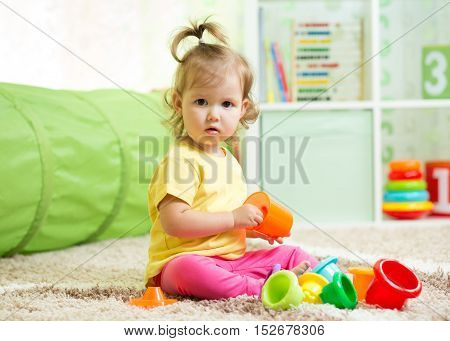 Little child playing with toys in home