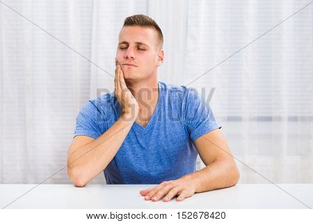 Photo of young man  having toothache and sitting at the table.
