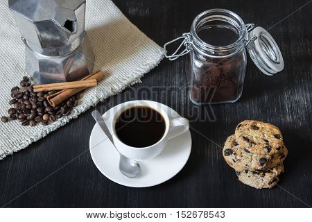Black coffee with italian moka pot and cookies. Cup of black coffee in front of italian moka pot on flax table-napkin, coffee beans and cinnamon, chocolate chip cookies and jar with ground coffee on black vintage wood table.