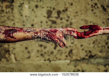 Two zombie hands male and female of man war soldier and girl woman with bloody wounds and red blood on skin