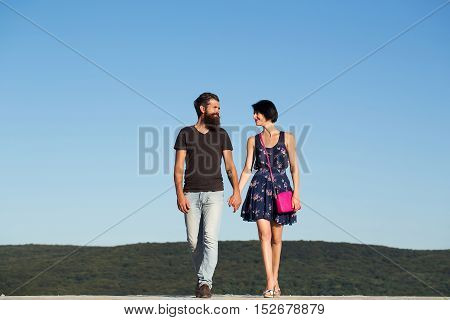 Young couple of handsome man bearded hipster and beautiful brunette woman walk and hold hands on blue sky