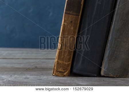 Stack of old books on a wooden bookshelf close up with copy space on the background of a blue wall