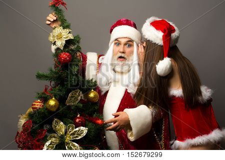 Amazed santa claus man with white beard in new year red suit listens to whisper of pretty sexy girl