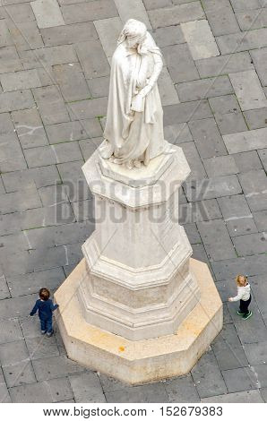 Verona Italy 27 October 2013: Childrens play around the tall white statue of Dante Alighieri