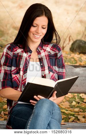 Beautiful young woman reading a book sitting on a bench in park at fall