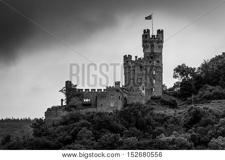 Sooneck Castle at the outermost tip of the Soon Forest above Niederheimbach in cloudy weather on the Rhine River in Germany. Black and white photography.