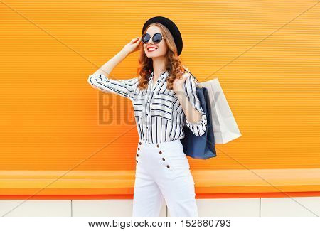 Fashion Elegant Young Smiling Woman Model With Shopping Bags Wearing A Black Hat White Pants Over Co