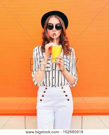Fashion Pretty Woman Model With Fresh Fruit Juice Cup Wearing Black Hat White Pants Over Colorful Or
