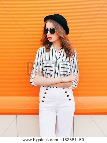 Pretty Fashion Woman Model Wearing Black Hat Sunglasses White Pants Over Colorful Orange Background