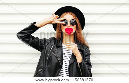 Cool Young Girl With Red Lollipop Heart Wearing Fashion Black Hat Leather Jacket Over White Urban Ba