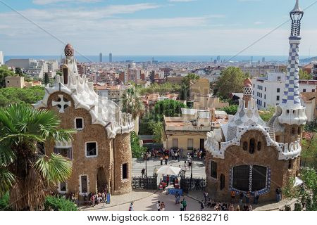 Barcelona, Spain - 24 September 2016: Park Guell entrance gate and buildings. View of Barcelona City and visitors at the park entrance on the south.