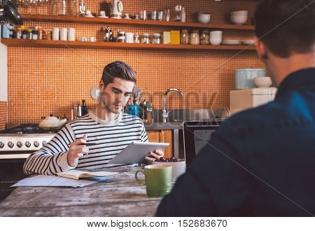 Young friends sitting at the kitchen table at home using a laptop and digital tablet while working together on their home based business