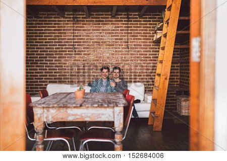Portrait of an affectionate young gay couple sitting on teh sofa together in their loft apartment