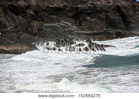 Wave splashing over a rock on the beach of Puertito de los Molinos on Fuerteventura. Canary Island Spain