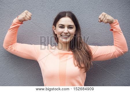 young sporty woman showing off her muscles and smiles