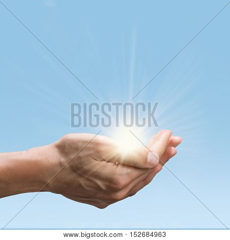 Close up of man hands holding a bright sun. Open palm gesture of male hand while hold the green energy of sun. Environmental conservation and green energy concept.