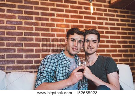 Portrait of an affectionate young gay couple sitting at home together on their living room sofa talking and drinking red wine