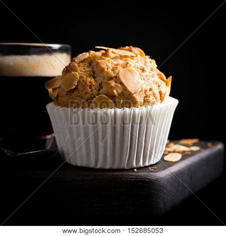 Delicious homemade coconut cinnamon muffin with almond flakes on black background. Healthy food concept with copy space.