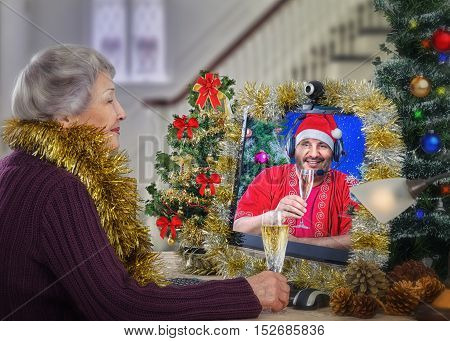 Lonely aged woman gets call online from her psychologist on Christmas Eve. Mature man dressed up as Santa Claus wishes gray-haired contented woman a Merry Christmas and offers a toast with white sparkling wine