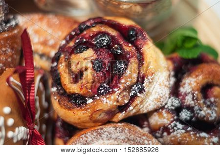 baked sweet rolls with black currant and powdered sugar