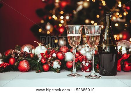 Christmas Still Life - Two Glasses Of Champagne With Xmas Decorations And Christmas Tree On Blurred