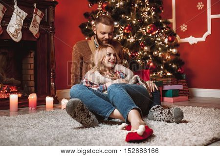 A Couple Of Lovers Resting By The Fireplace In The Christmas Room. Feet In Woolen Socks Warming In W