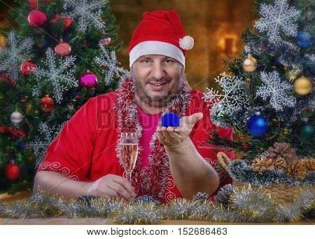 Portrait of sitting at the desk Santa Claus holding blue jewelry box by left hand. In right hand there is a glass of white dry wine. Horizontal shot on blurry indoors background with decorated Christmas trees