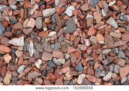 Top view of large red and gray gravel stones texture