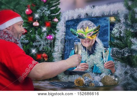Santa Claus wishes gray-haired senior woman in feather mask a Merry Christmas. They are toasting with white dry wine during online video conversation