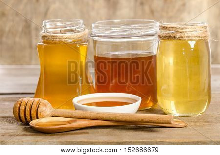 Three Jars,the Bowl, The Spoon With A Honey On Wooden Background