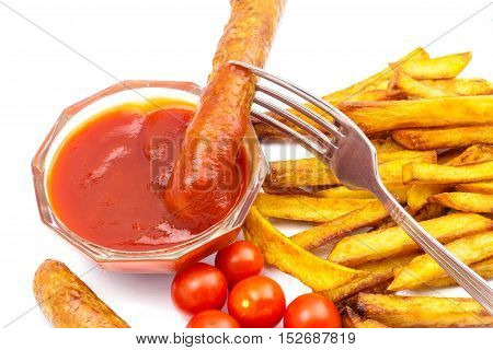 Homemade fast food portion of french fries ketchup cherry tomato and grilled sausages on fork isolated on white background